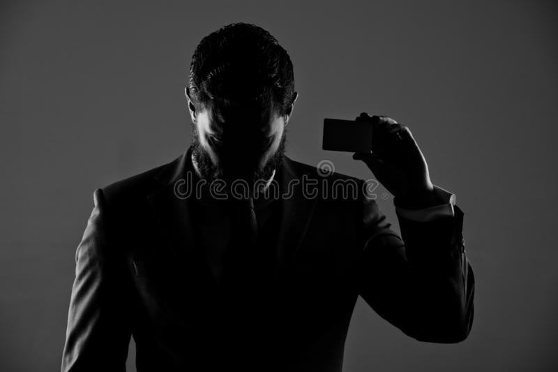 Ceo or man with business or credit card, business ethics. Shady business. ceo or man with business or credit card in blue formal outfit in shadow on grey royalty free stock image