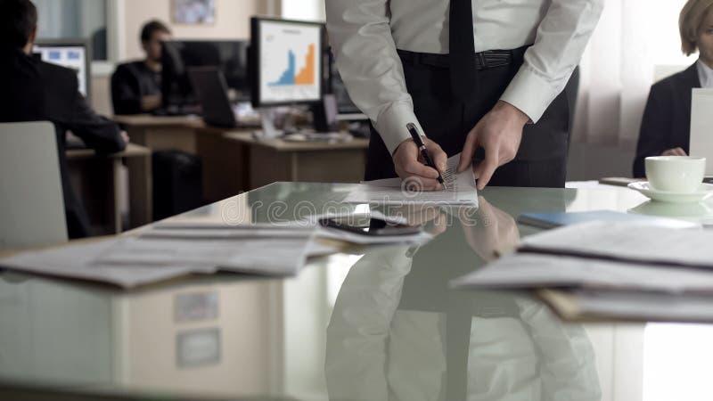 CEO maschio che firma contratto, impiegati che lavorano al fondo, lavoro di ufficio in ufficio fotografie stock libere da diritti