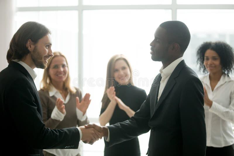 Ceo met team die zwarte manager waarderen door handdruk en applau royalty-vrije stock afbeeldingen