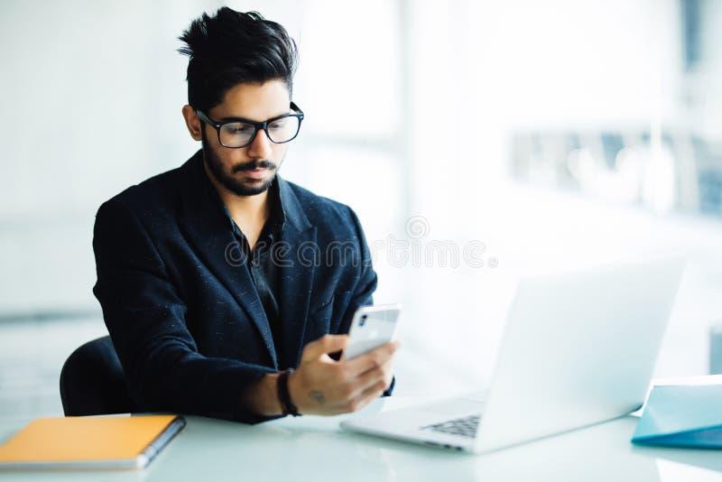 CEO novo do indiano da empresa em seu escritório para negócios na mesa, lendo o texto no smartphone imagens de stock royalty free