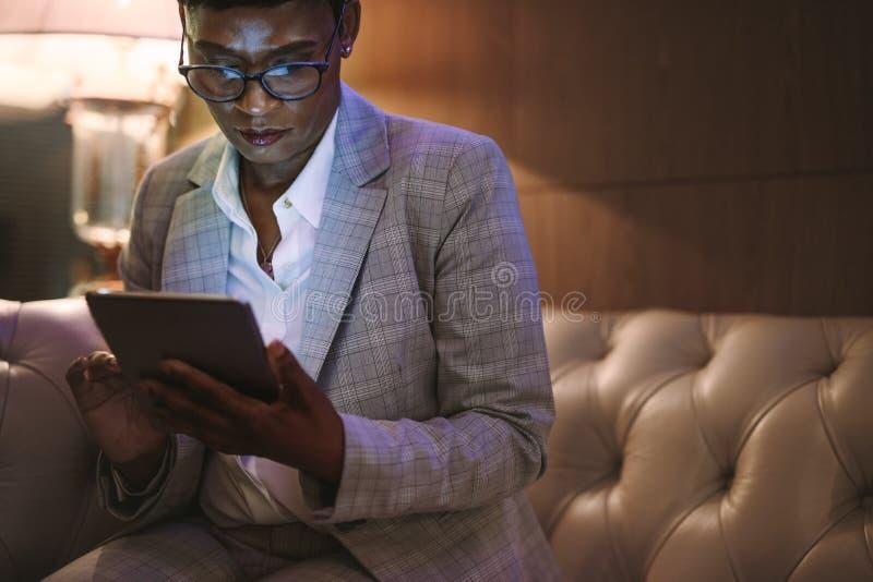 CEO op zakenreis die tabletpc in hotelhal met behulp van stock foto's