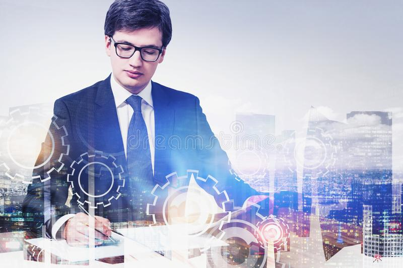 CEO signing documents in city, gears. Serious young businessman in glasses signing documents in city with double exposure of gears. Concept of well organized stock images