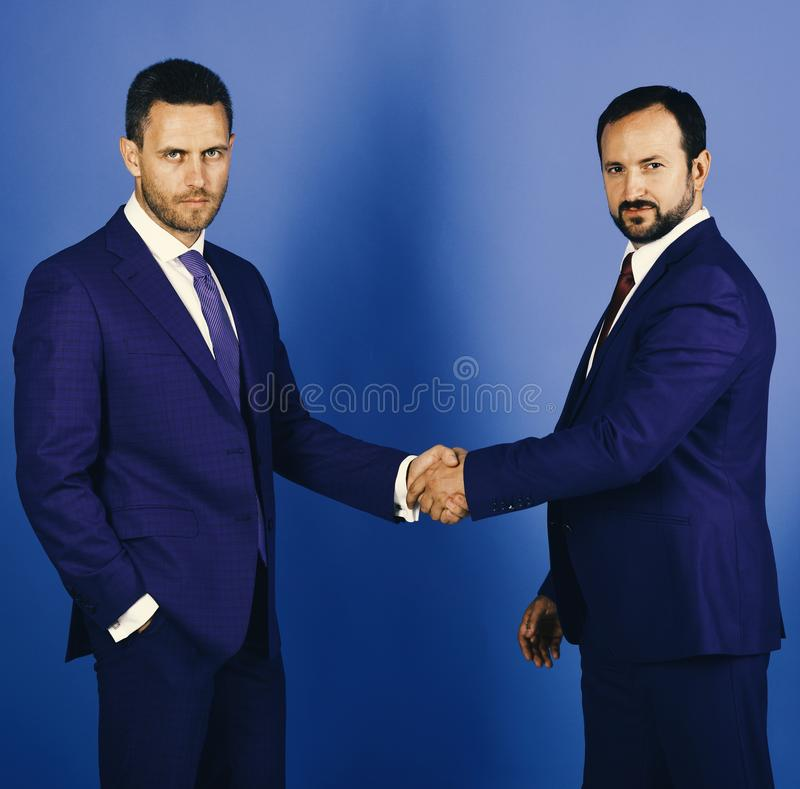 CEOs shake hands on blue background. Business and compromise. Concept. Businessmen wear smart suits and ties. Men with beard and serious faces make deal or royalty free stock photos