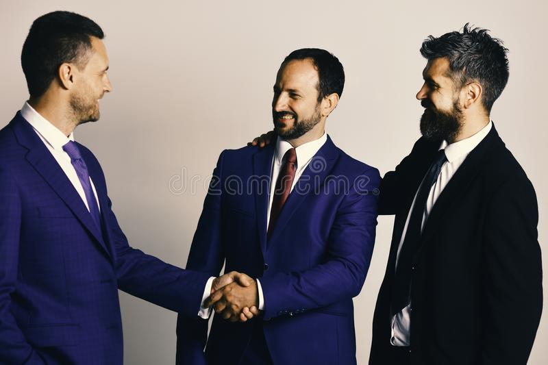 CEOs shake hands on light grey background. Business and compromise. CEOs shake hands on light grey background. Business agreement and compromise concept royalty free stock images