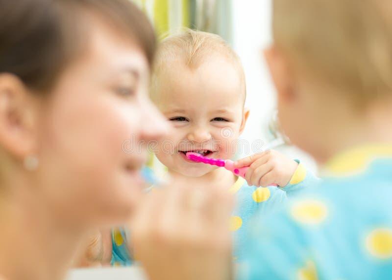 Cepillado de dientes de enseñanza del niño de la madre foto de archivo