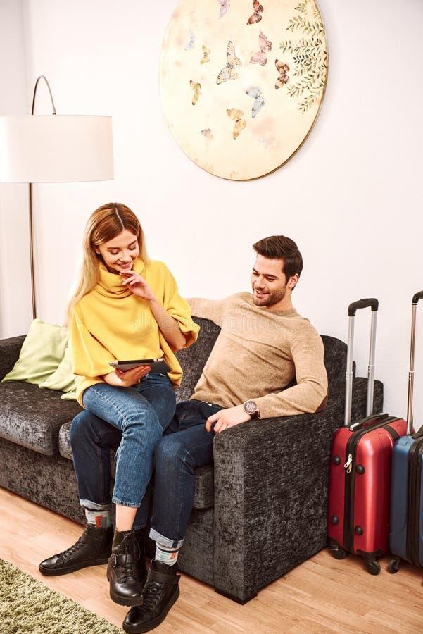 Cepillado de las vacaciones Pares maduros felices con las maletas que buscan en la habitación foto de archivo libre de regalías