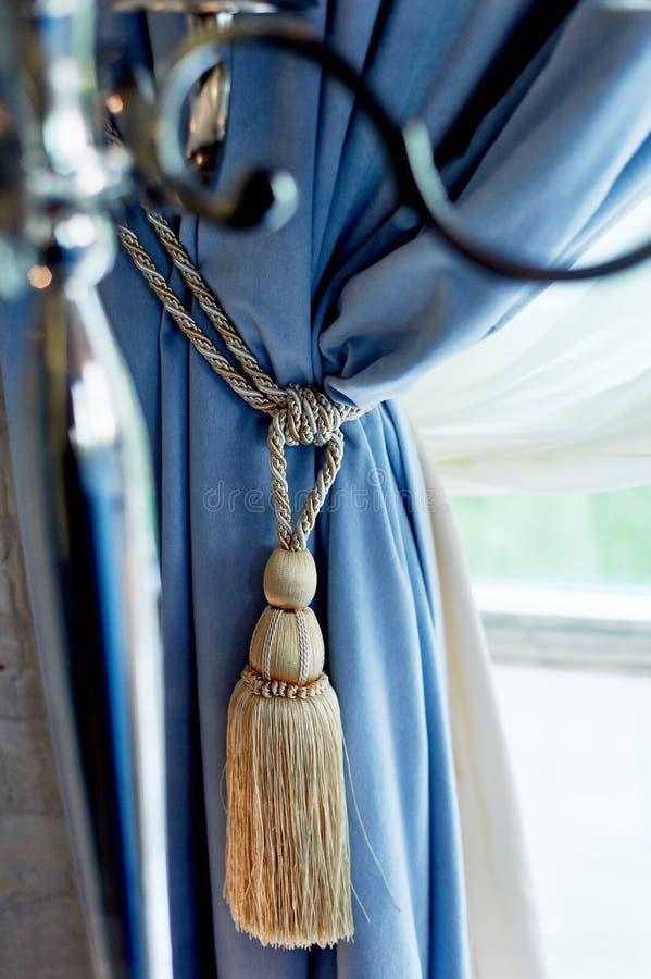 Cepille con los hilos en las cortinas azules Ventana de madera ligera Interior cl?sico imagen de archivo libre de regalías