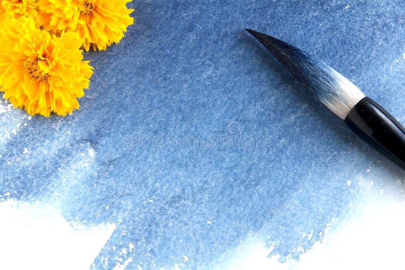 Cepillo caligráfico manchado con la pintura azul en una hoja del papel de la acuarela con la mancha del añil fotos de archivo