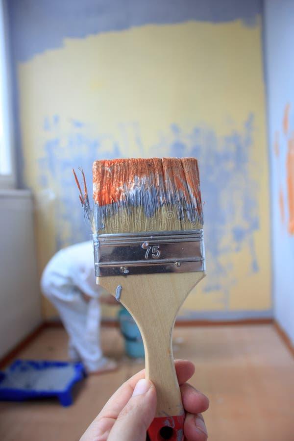 Cepillo con la pintura anaranjada y blanca como la renovación y creación imagenes de archivo