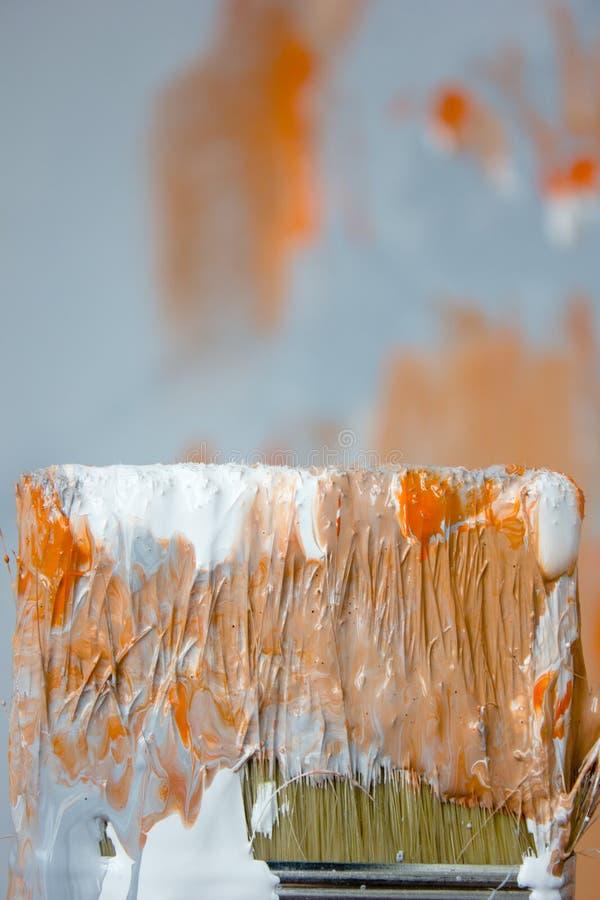 Cepillo con la pintura anaranjada y blanca como la renovación y creación fotografía de archivo