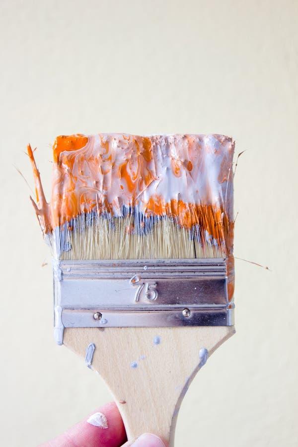Cepillo con la pintura anaranjada y blanca como la renovación y creación foto de archivo