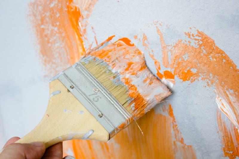 Cepillo con la pintura anaranjada y blanca como la renovación y creación fotos de archivo