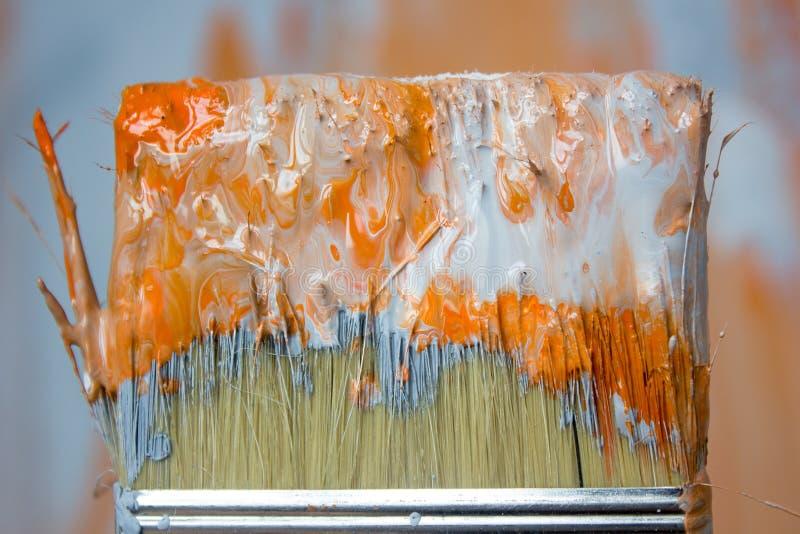 Cepillo con la pintura anaranjada y blanca como la renovación y creación fotografía de archivo libre de regalías