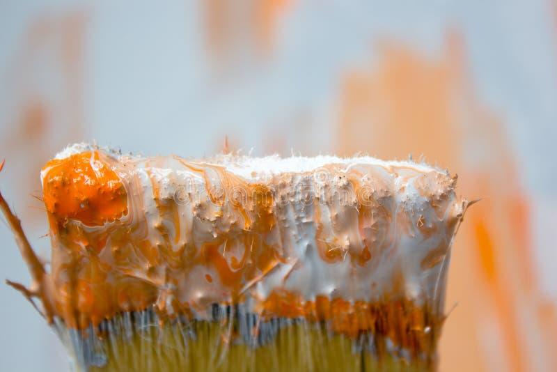 Cepillo con la pintura anaranjada y blanca como la renovación y creación imagen de archivo libre de regalías