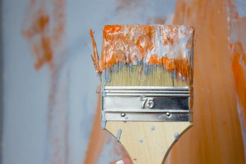 Cepillo con la pintura anaranjada y blanca como la renovación y creación fotos de archivo libres de regalías