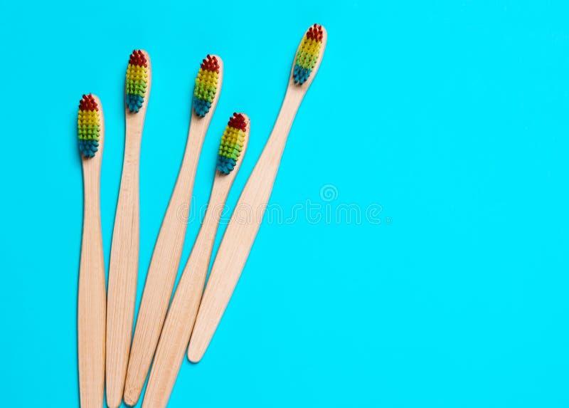 cepillo de dientes de bambú ecológico, orgánico sobre fondo azul de cerdas coloradas fotografía de archivo