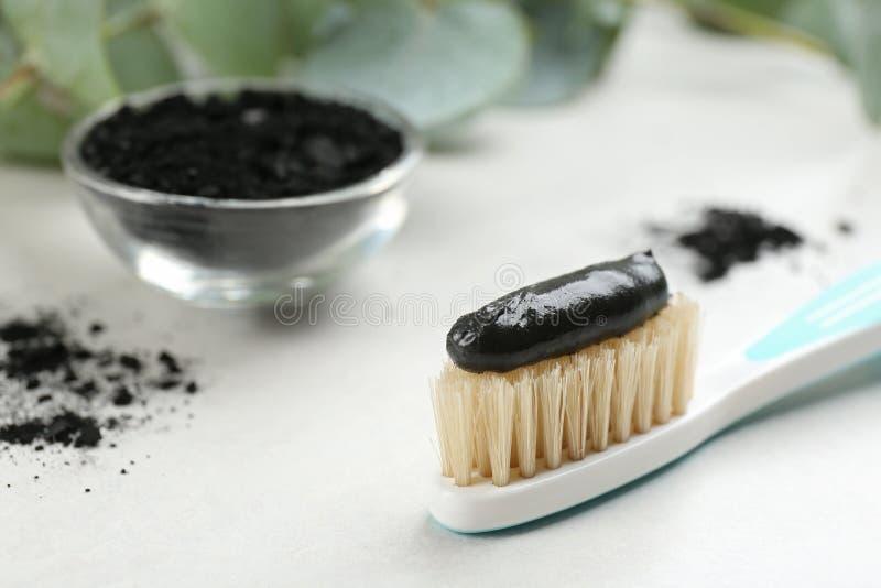 Cepillo de dientes con cerdas naturales y pasta de carbón vegetal sobre mesa blanca Espacio para texto fotografía de archivo libre de regalías