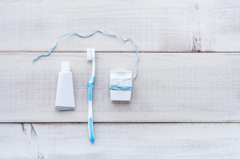 Cepillo de dientes, crema dental y seda dental en una parte posterior resistida de madera fotografía de archivo