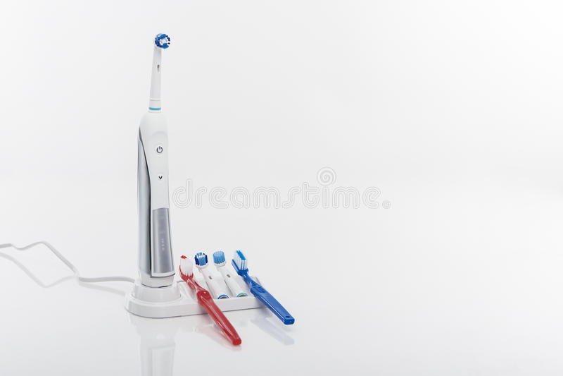 Cepillo de dientes eléctrico moderno en cuna con las cabezas de repuesto del cepillo fotos de archivo