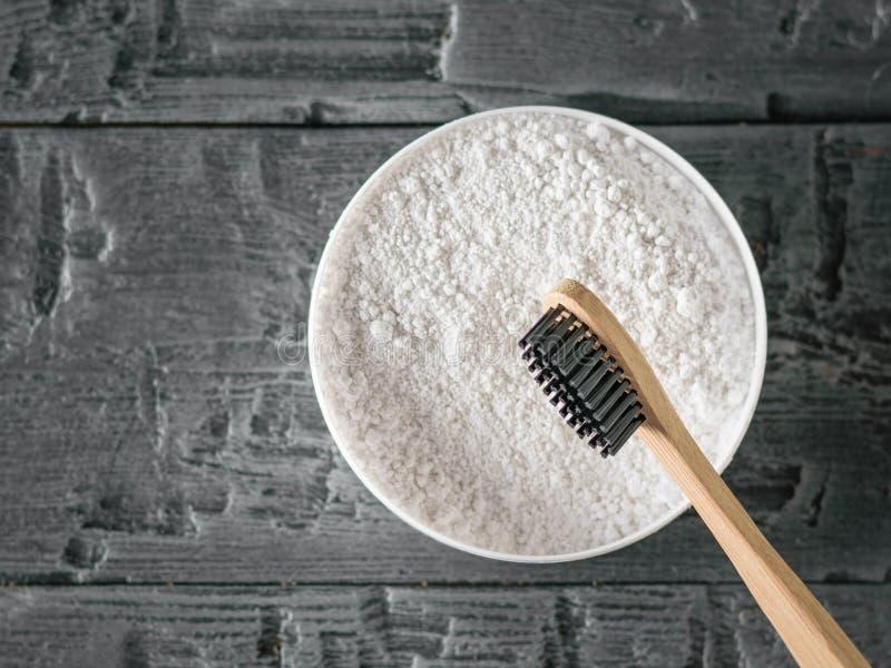 Cepillo de dientes de madera con las cerdas negras y polvo de la limpieza del diente en la tabla de madera oscura La visión desde imagen de archivo libre de regalías
