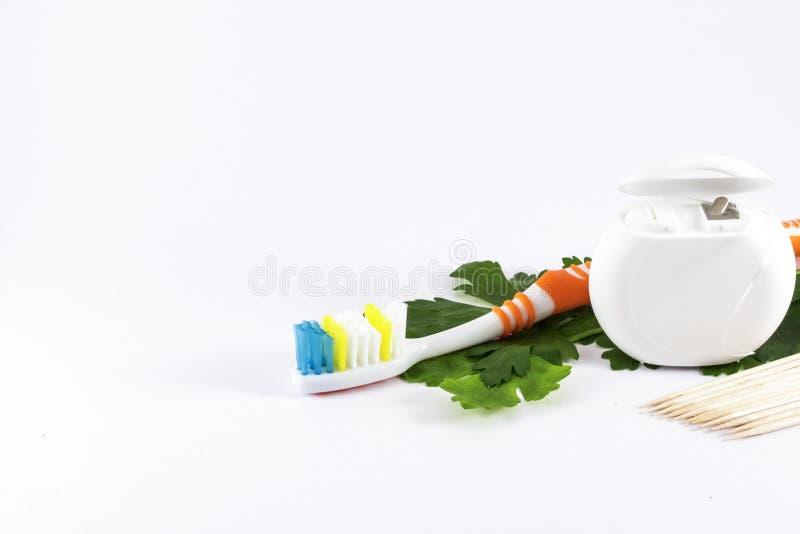 Cepillo de dientes, palillos y seda dental en el fondo blanco imagenes de archivo