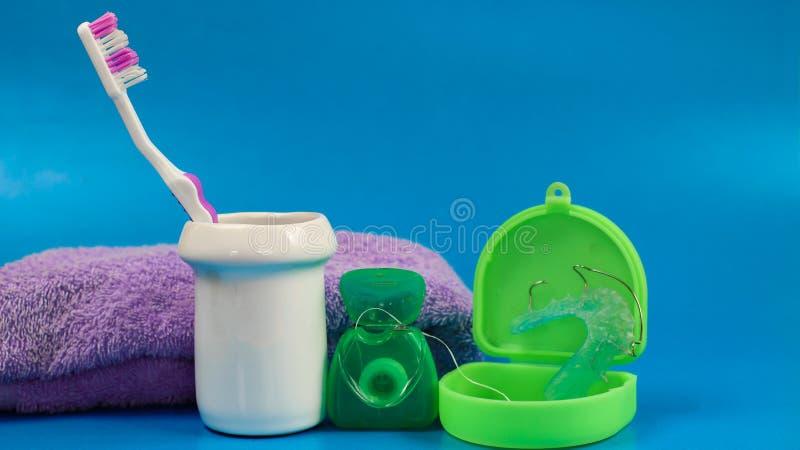 cepillo de dientes rosado con seda dental y objeto sano verde del criado del fondo del color limpio blanco púrpura dental de la h fotos de archivo