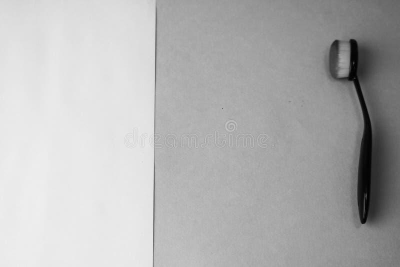 Cepillo de madera hecho de la pelusa natural para aplicar tono en un fondo blanco y negro Endecha plana Visión superior imagen de archivo libre de regalías