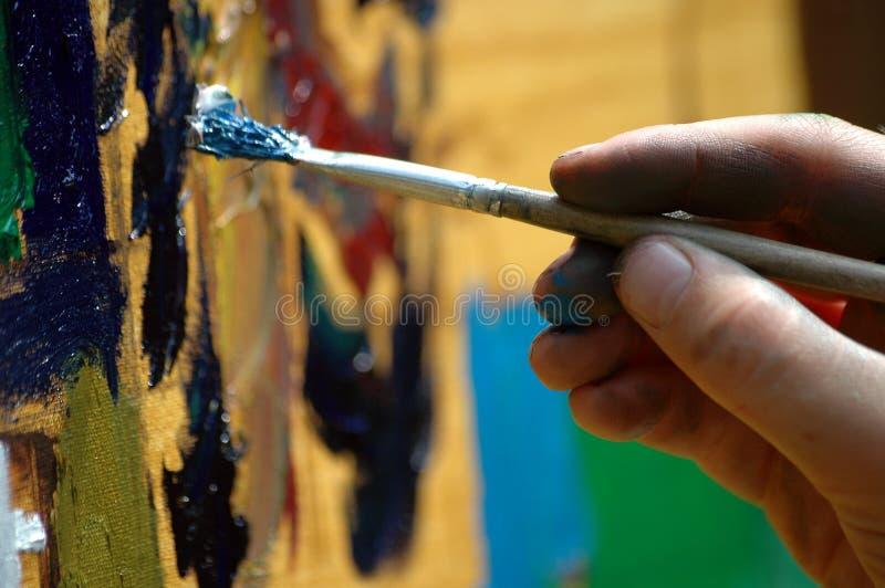 Cepillo de pintura en niños \ 'mano de s fotografía de archivo libre de regalías
