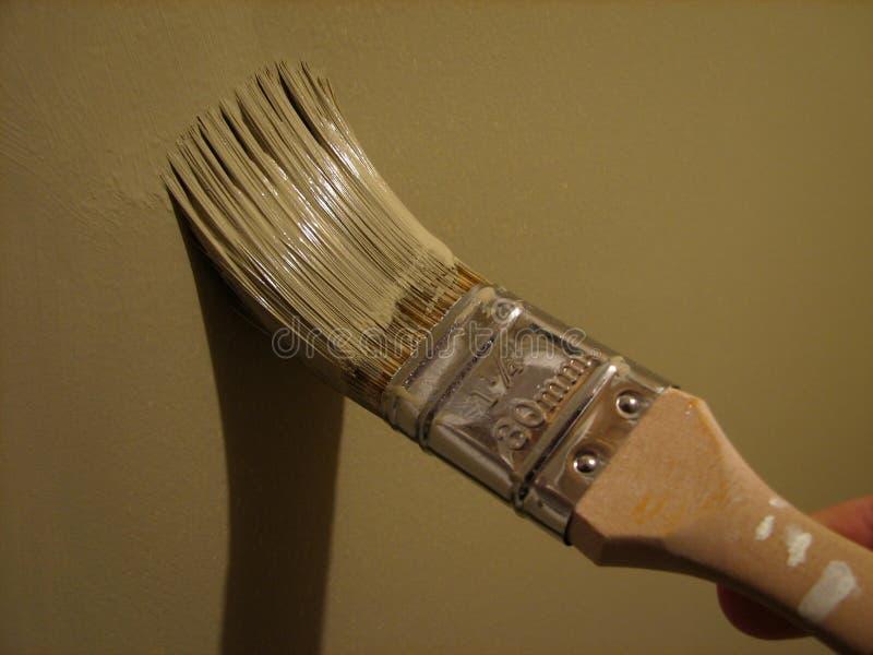 Cepillo de pintura que pinta una pared fotos de archivo