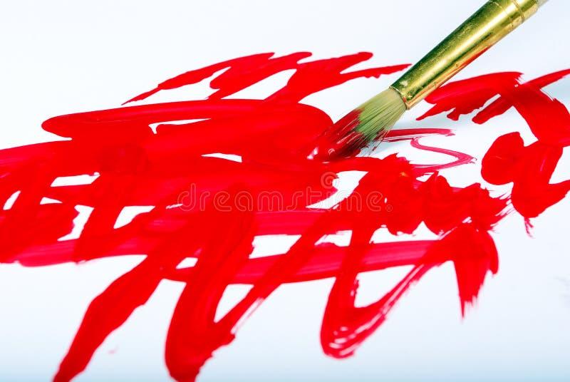 Cepillo del artista y pinceladas rojas en blanco fotos de archivo