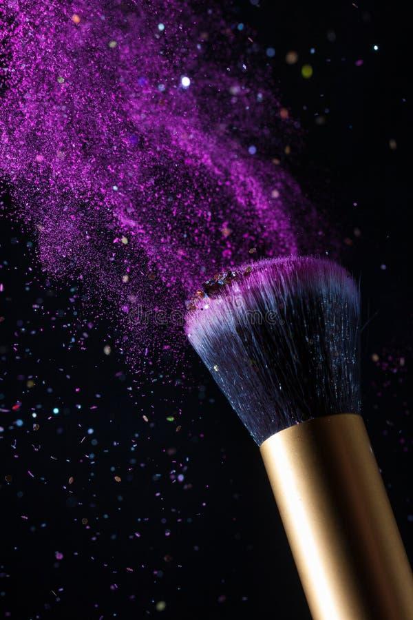 Cepillo del maquillaje de los cosméticos y fondo de la explosión de polvo del polvo imagen de archivo