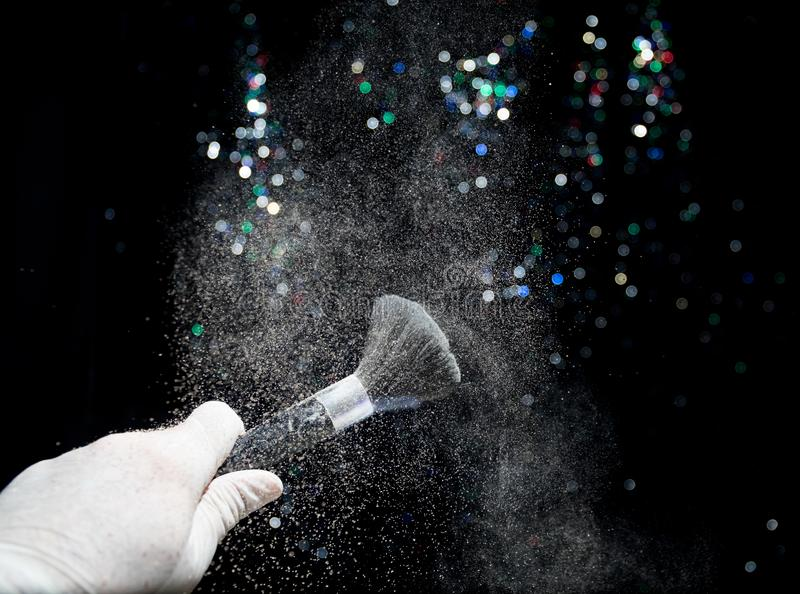 Cepillo del maquillaje a disposición con el polvo cosmético en fondo oscuro con la luz y el humo Pulverice el chapoteo en oscurid imagen de archivo