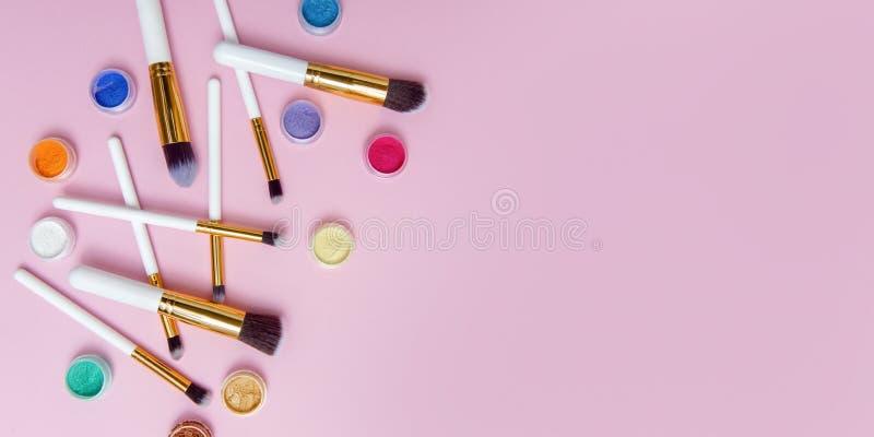Cepillo del maquillaje en fondo rosado con el polvo colorido del pigmento Visi?n superior imagenes de archivo