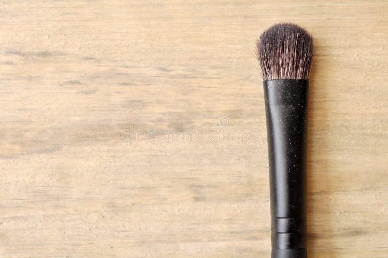 Cepillo del maquillaje en la tabla de madera imagen de archivo libre de regalías