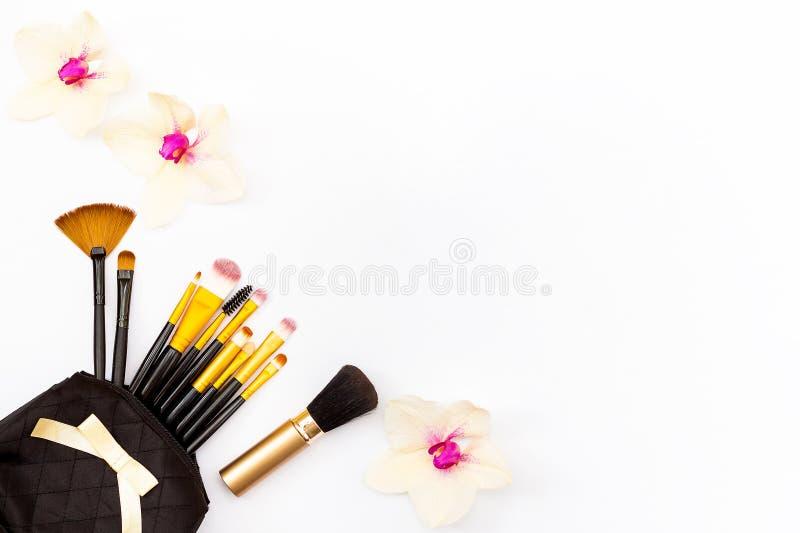 Cepillo del maquillaje en mi monedero y orquídea de algunas flores en un fondo blanco Concepto mínimo de belleza foto de archivo