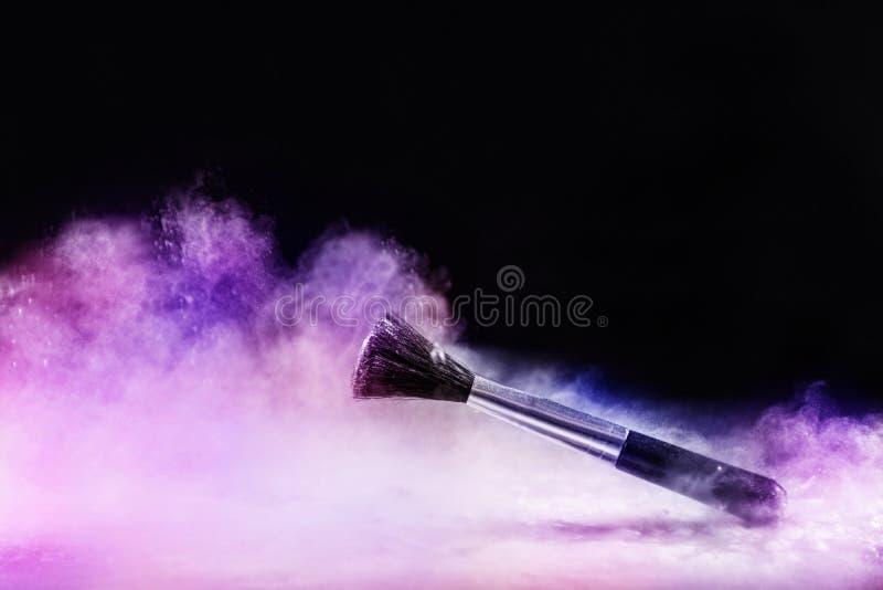 Cepillo del maquillaje en niebla colorida del polvo de la explosión del polvo en negro foto de archivo