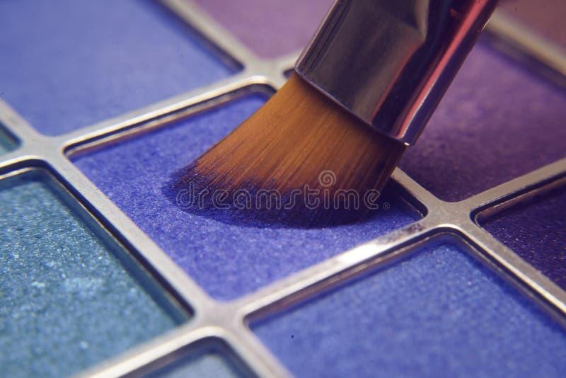 Cepillo del maquillaje en sombras azules Sombras brillantes para el verano Marco macro de sombras Cosméticos brillantes, colores  imagen de archivo libre de regalías