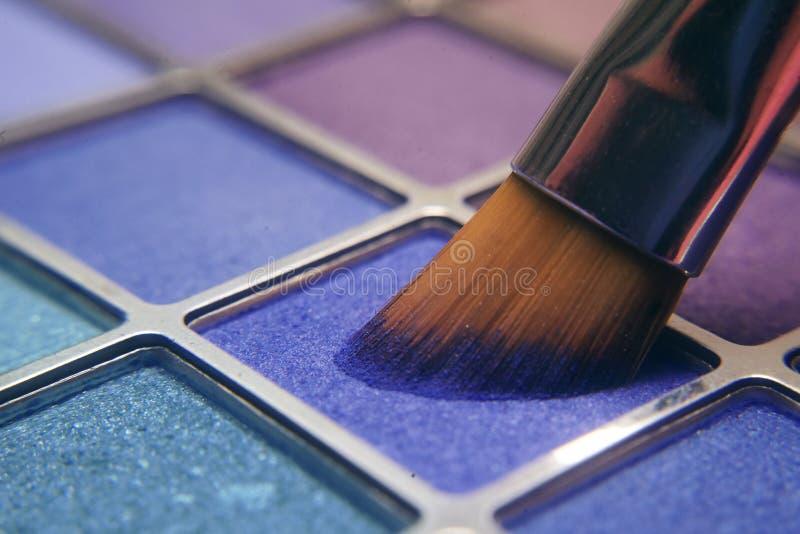 Cepillo del maquillaje en sombras azules Sombras brillantes para el verano Marco macro de sombras Cosméticos brillantes, colores  fotos de archivo