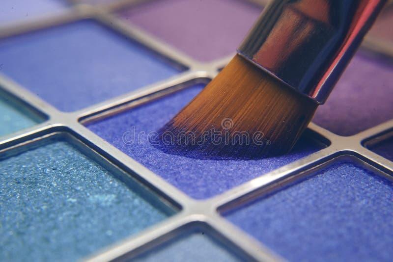Cepillo del maquillaje en sombras azules Sombras brillantes para el verano Marco macro de sombras Cosméticos brillantes, colores  fotos de archivo libres de regalías