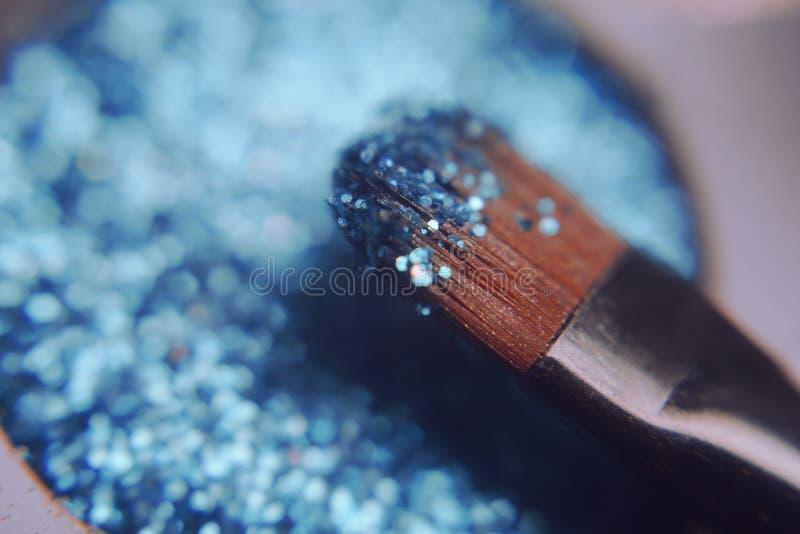 Cepillo del maquillaje en sombras brillantes azules Sombras brillantes con brillo del brillo imagen de archivo