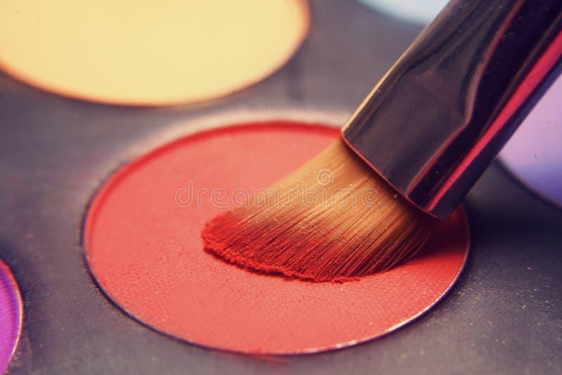 Cepillo del maquillaje en sombras rojas Sombras brillantes para el verano Marco macro de sombras Cosméticos brillantes, colores d fotografía de archivo