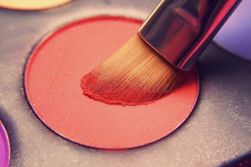 Cepillo del maquillaje en sombras rojas Sombras brillantes para el verano Marco macro de sombras Cosméticos brillantes, colores d foto de archivo libre de regalías