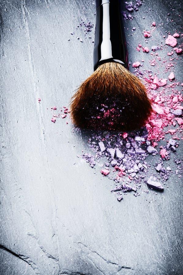 Cepillo del maquillaje y sombras de ojos machacadas fotos de archivo