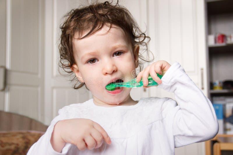 Cepillo del niño del bebé sus dientes correctamente con un cepillo de dientes verde imagen de archivo