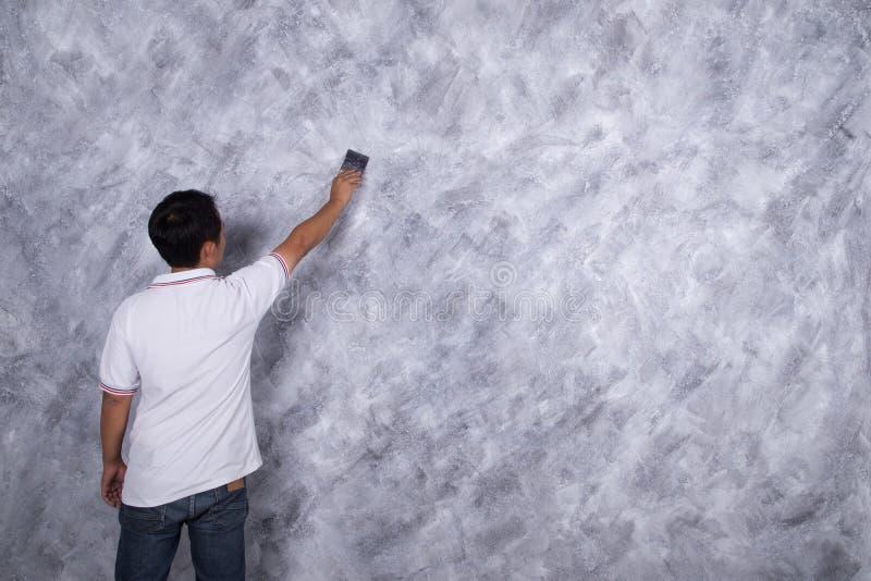 Cepillo del uso del trabajador para el estilo concreto del desván de la pintura del color en la pared imágenes de archivo libres de regalías