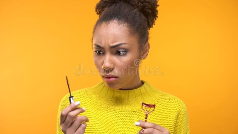 Cepillo femenino joven sorprendido del bigudí y del rimel de la pestaña que se sostiene, extremidades de la belleza imagen de archivo