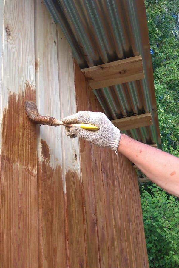 Cepillo hecho a mano para la pintura manual en una pared de madera foto de archivo