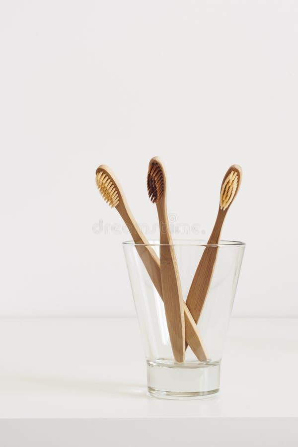 Cepillos de dientes de bambú con las cerdas naturales en vidrio en cuarto de baño escandinavo del estilo imagenes de archivo