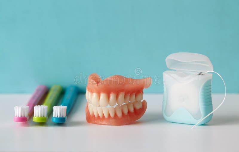 Cepillos de dientes coloridos, dentaduras y seda dental fotos de archivo
