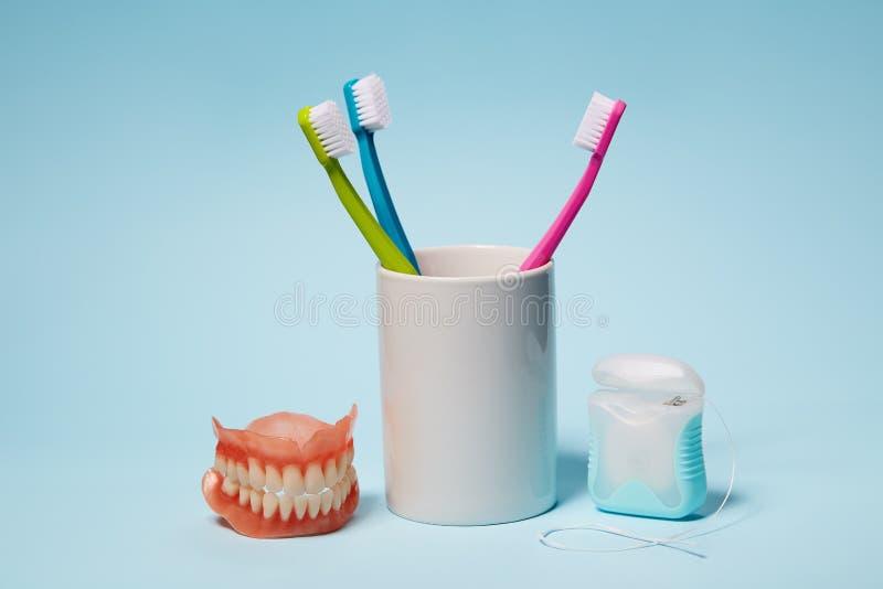 Cepillos de dientes coloridos, dentaduras y seda dental imágenes de archivo libres de regalías